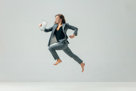 Happy business woman dancing and smiling in motion isolated over white studio background. Human emotions concept. The businesswoman, office, success, professional, , happiness, expression concepts Фото со стока - 115612235