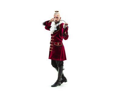 The young man wearing a traditional medieval costume of marquis posing at studio with whip. Fantasy, Antique, Renaissance concept