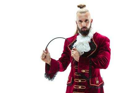 Der junge Mann in einem traditionellen mittelalterlichen Kostüm des Marquis posiert im Studio mit Peitsche. Fantasie, Antiquität, Renaissance-Konzept Standard-Bild