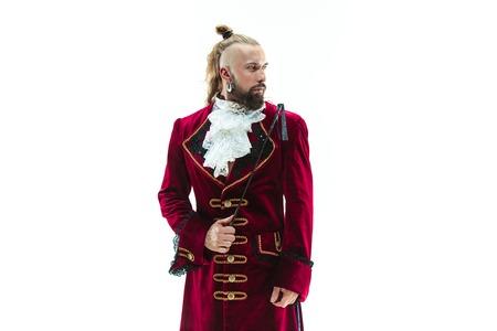 Der junge Mann in einem traditionellen mittelalterlichen Kostüm des Marquis posiert im Studio mit Peitsche. Fantasie, Antiquität, Renaissance-Konzept