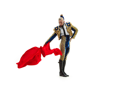 Torero in blue and gold suit or typical spanish bullfighter isolated over white studio background. The taming, achieving the goal, mortification, conquest, boss, leadership, battle, win, winner concept Stock Photo - 115612773