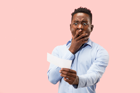Young afro man with a surprised unhappy failure expression bet slip on pink studio background. Human facial emotions and betting concept. Trendy colors Stock fotó