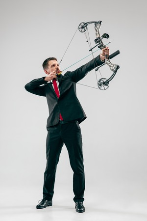 Businessman aiming at target with bow and arrow, isolated on gray studio background. The business, goal, challenge, competition, achievement concept