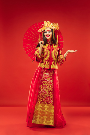 Chinese traditional graceful woman at studio over red background. Beautiful girl wearing national costume. Chinese New Year, elegance, grace, performer, performance, dance, actress, emotions concept