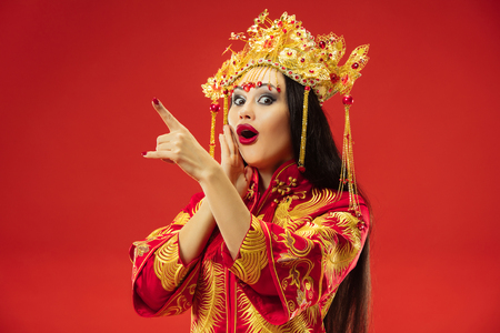 Chinese traditional graceful woman at studio over red Stock Photo