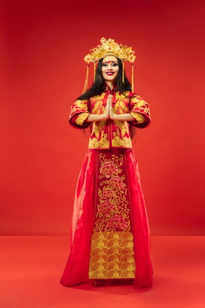Chinese traditional graceful woman at studio over red Imagens