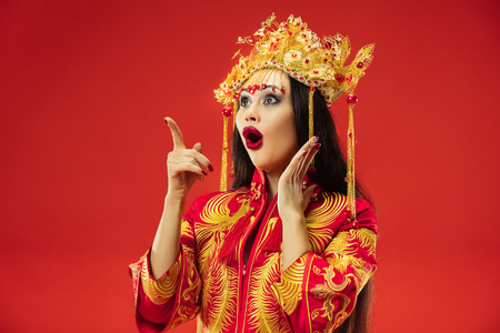Chinese traditional graceful woman at studio over red 版權商用圖片