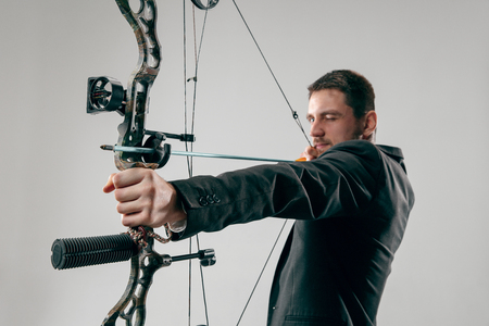 Businessman aiming at target with bow and arrow isolated on gray studio