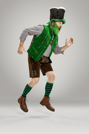 A smiling happy senior man in a leprechaun hat with beard running at studio.