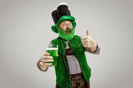 A smiling happy senior man in a leprechaun hat with green beer at studio. Stock Photo