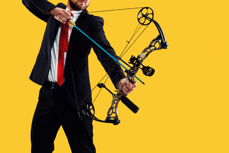 Businessman aiming at target with bow and arrow, isolated on yellow studio Banco de Imagens