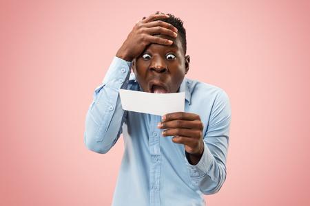 Jeune homme afro avec un pari d'expression d'échec mécontent surpris sur un studio rose