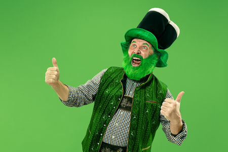 A smiling surprised happy senior man in a leprechaun hat with beard at green studio.