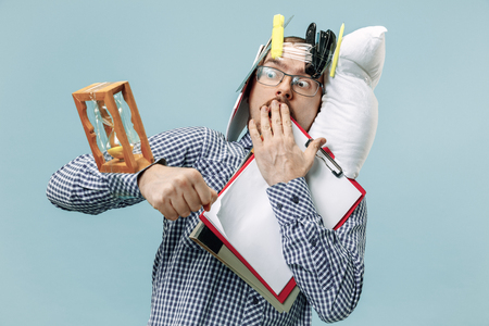 Hombre asustado cansado durmiendo en casa u oficina con demasiado trabajo. Foto de archivo