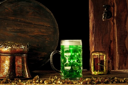 The wooden barrel  with lots of gold coins and a large mug of beer with a green bow.