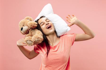Mujer feliz cansada durmiendo en casa u oficina con demasiado trabajo. Empresaria aburrida con almohada y oso de juguete. El ocupado, aburrido, preocupado, llegar tarde, preocupado, el día del sueño, el concepto introuble Foto de archivo