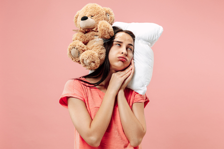 Tired happy woman sleeping at home or office having too much work. Bored businesswoman with pillow and toy bear. The busy, boring, worried, be late, concerned, sleep day, introuble concept