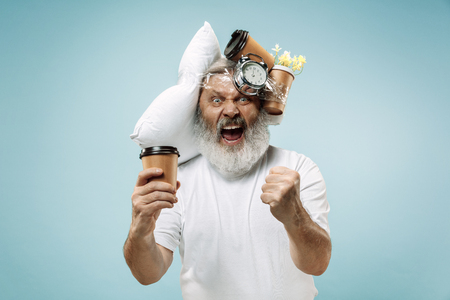 Surprised senior man screaming after sleeping at home or office having too much work. Bored businessman with pillow and hourglass. The busy, boring, worried, be late, concerned, sleep day, introuble concept