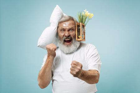 Hombre mayor sorprendido gritando después de dormir en casa u oficina con demasiado trabajo. Hombre de negocios aburrido con almohada y reloj de arena. El ocupado, aburrido, preocupado, llegar tarde, preocupado, el día del sueño, el concepto introuble Foto de archivo