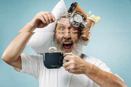 Surprised senior man drinking tea after sleeping at home or office having too much work. Bored businessman with pillow and hourglass. The busy, boring, worried, be late, concerned, sleep day, introuble concept Banque d'images - 116257254