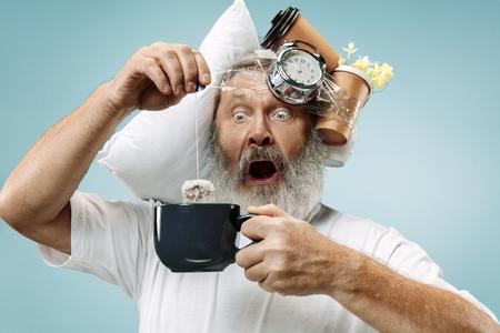 Hombre mayor sorprendido bebiendo té después de dormir en casa u oficina con demasiado trabajo. Hombre de negocios aburrido con almohada y reloj de arena. El ocupado, aburrido, preocupado, llegar tarde, preocupado, el día del sueño, el concepto introuble Foto de archivo