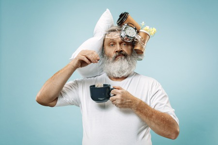 Surprised senior man drinking tea after sleeping at home or office having too much work. Bored businessman with pillow and hourglass. The busy, boring, worried, be late, concerned, sleep day, introuble concept