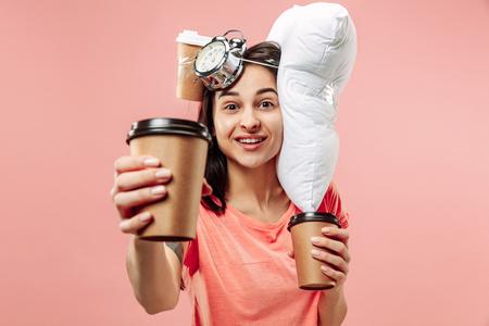Mujer feliz cansada tomando café en casa u oficina con demasiado trabajo. Empresaria aburrida con almohadas y tazas de café. El ocupado, aburrido, preocupado, llegar tarde, preocupado, día de sueño, concepto introuble Foto de archivo