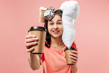 Tired happy woman drinking coffee at home or office having too much work. Bored businesswoman with pillow and coffee cups. The busy, boring, worried, be late, concerned, sleep day, introuble concept