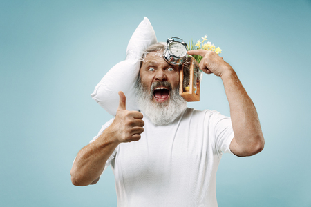 Surprised senior man screaming after sleeping at home or office having too much work. Bored businessman with pillow and hourglass. The busy, boring, worried, be late, concerned, sleep day, introuble concept Banque d'images - 116257262