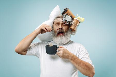 Hombre mayor sorprendido bebiendo té después de dormir en casa u oficina con demasiado trabajo. Hombre de negocios aburrido con almohada y reloj de arena. El ocupado, aburrido, preocupado, llegar tarde, preocupado, el día del sueño, el concepto introuble