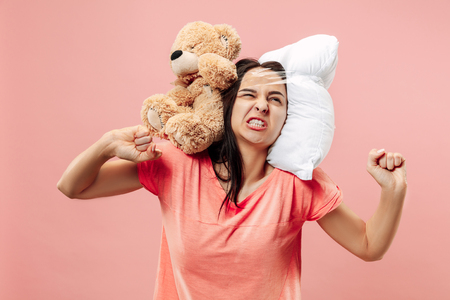 Tired happy woman sleeping at home or office having too much work. Bored businesswoman with pillow and toy bear. The busy, boring, worried, be late, concerned, sleep day, introuble concept Banque d'images - 116257265