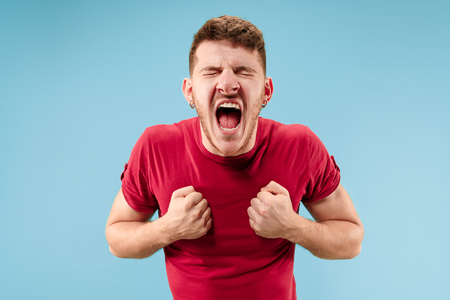 Screaming, hate, rage. Crying emotional angry man screaming on blue studio background. Emotional, young face. male half-length portrait. Human emotions, facial expression concept. Trendy colors