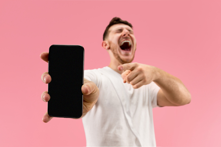 Young handsome man showing smartphone screen over pink background with a surprise face. Human emotions, facial expression concept. Trendy colors