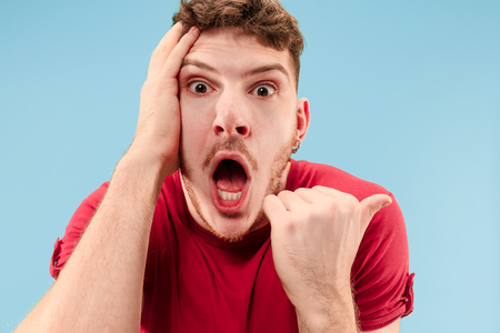 Wauw. Aantrekkelijk mannelijk half-lengte voorportret op blauwe studio achtergrondgeluid. Jonge emotionele verrast bebaarde man met open mond. Menselijke emoties, gezichtsuitdrukking concept. Trendy kleuren