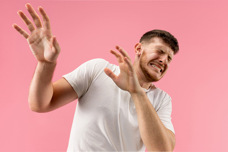 Im afraid. Fright. Portrait of the scared man. Business man standing isolated on trendy pink studio background. male half-length portrait. Human emotions, facial expression concept