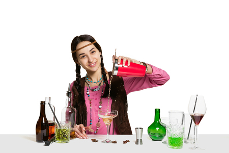 Expert female barman is making cocktail at studio isolated on white background. International barman day, bar, alcohol, restaurant, party, pub, nightlife, cocktail, nightclub concept