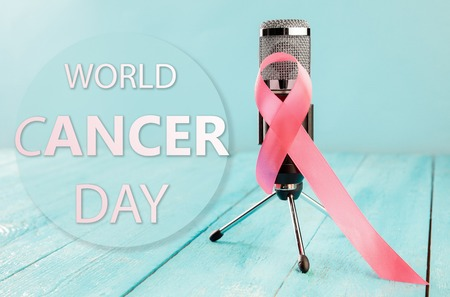 The text world cancer day and a pink ribbon with microphone on wooden table background. The cancer, health, breast, awareness, campaign, disease, help, care, support, hope, illness, survivor healthcare concept Stock Photo