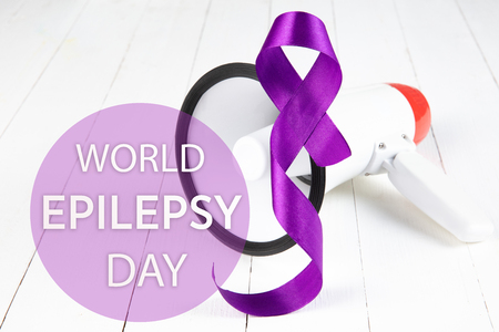 International or world Epilepsy Day concept. The text and a purple ribbon with megaphone on a white wooden table background. The health, breast, awareness, campaign, disease, help, care, support, hope, illness, survivor, healthcare concept