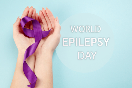 International or world Epilepsy Day concept. The text and a purple ribbon with female hands on a white wooden table background. The health, breast, awareness, campaign, disease, help, care, support, hope, illness, survivor, healthcare concept