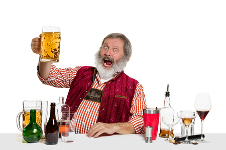The senior expert male barman with beer at studio isolated on white background. International barman day, bar, alcohol, restaurant, beer, party, pub, St. Patricks Day celebration concept
