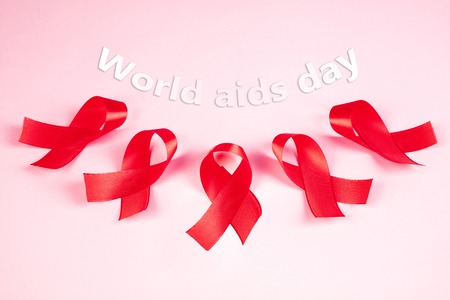 Aids Awareness Sign Red Ribbons on pink background . World Aids Day concept. The health, help, care, support, hope, illness, healthcare concept