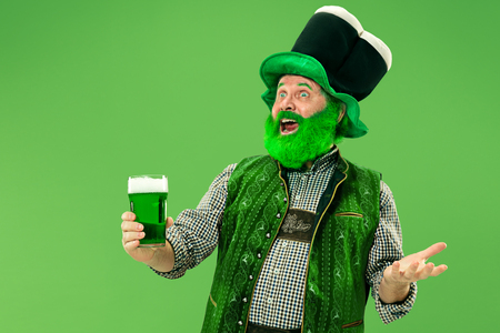 A smiling happy senior man in a leprechaun hat with green beer at studio. He celebrates St. Patricks Day. The celebration, festive, beer, holiday, alcohol, party concept