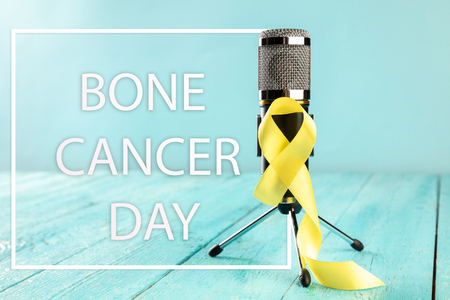 Yellow ribbon symbolic color for Sarcoma Bone cancer awareness and suicide prevention on aged wood with microphone. The cancer, health, help, care, support, hope, illness, healthcare concept