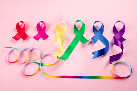 World cancer day on February 4. The colorful awareness ribbons - blue, red, green, pink and yellow color on pink background for supporting people living and illness. Healthcare and medicine concept Stock Photo - 116285947