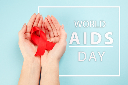 Aids Awareness Sign Red Ribbon with female hands on blue background . World Aids Day concept. The health, help, care, support, hope, illness, healthcare concept