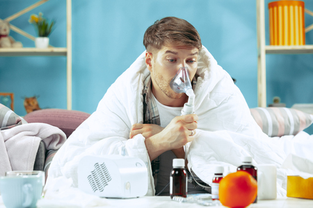 Bearded sick man with flue sitting on sofa at home covered with warm blanket and using an inhaler when coughing. The illness, influenza, pain concept. Relaxation at Home. Healthcare Concepts.