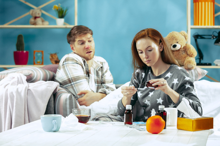 Sick man with fever lying in bed having temperature. The his wife take care for him. The illness, influenza, pain, family concept. Relaxation at Home. Healthcare Concepts. Stock Photo