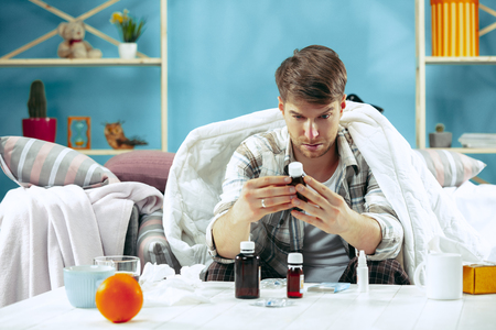 Bearded sick man with flue sitting on sofa at home covered with warm blanket and drinking syrup from cough. The illness, influenza, pain concept. Relaxation at Home. Healthcare Concepts.