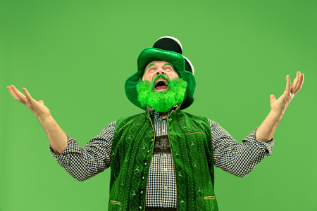 A smiling surprised happy senior man in a leprechaun hat with beard at green studio. He celebrates St. Patricks Day. The celebration, festive, beer, holiday, alcohol, party, human emotions concept