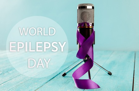 International or world Epilepsy Day concept. The text and a purple ribbon with microphone on a wooden table background. The health, breast, awareness, campaign, disease, help, care, support, hope, illness, survivor, healthcare concept